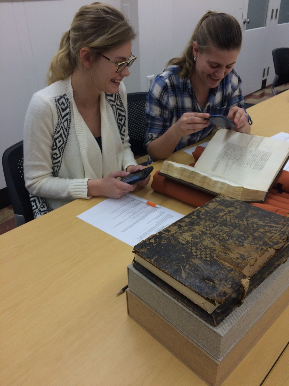 Image of two students examining a book