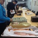 Students examining historic clothing and dolls