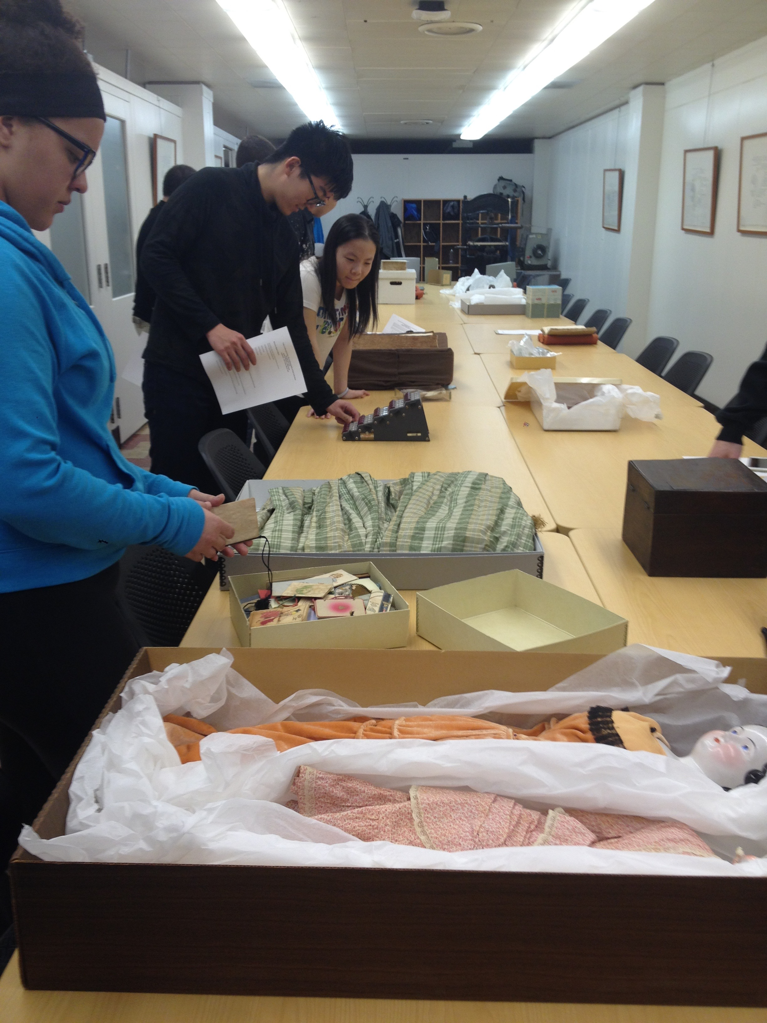 Students examining historic clothing and dolls