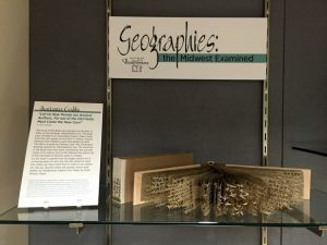 Geographies exhibition title card with example book