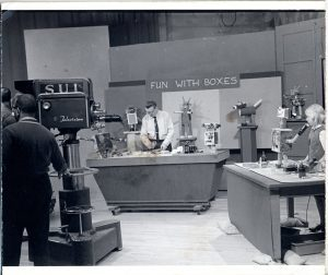 Fun with boxes: man on tv set with robots made of boxes