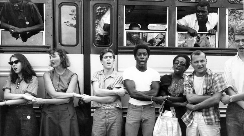 Students and Civil Rights activists holding hands in front of bus during Freedom Summer