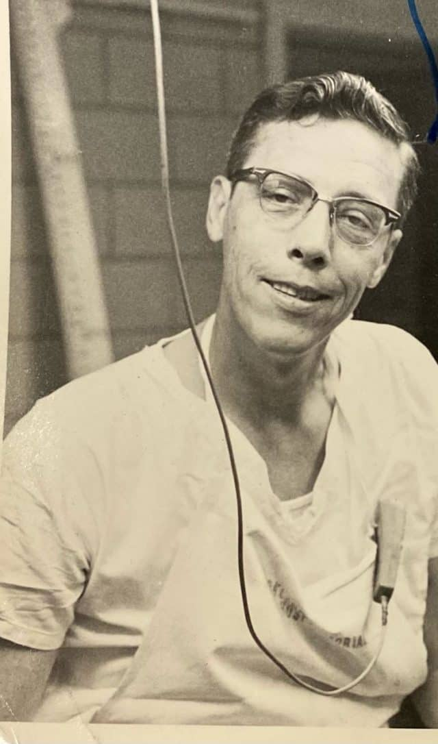 Black and white photo of Earl F. Rose with wearing horn-rimmed glasses and white scrubs