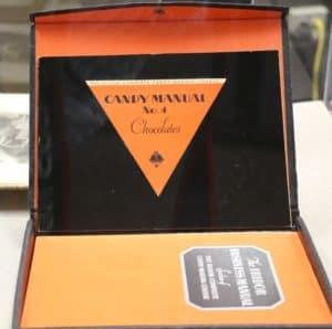 Bright orange and black box with a chocolate manual inside