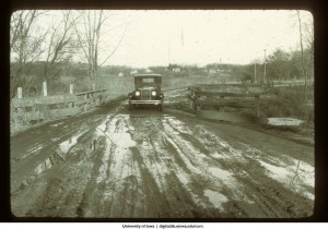 Automobile crossing a bridge on a dirt road, Iowa, 1922
