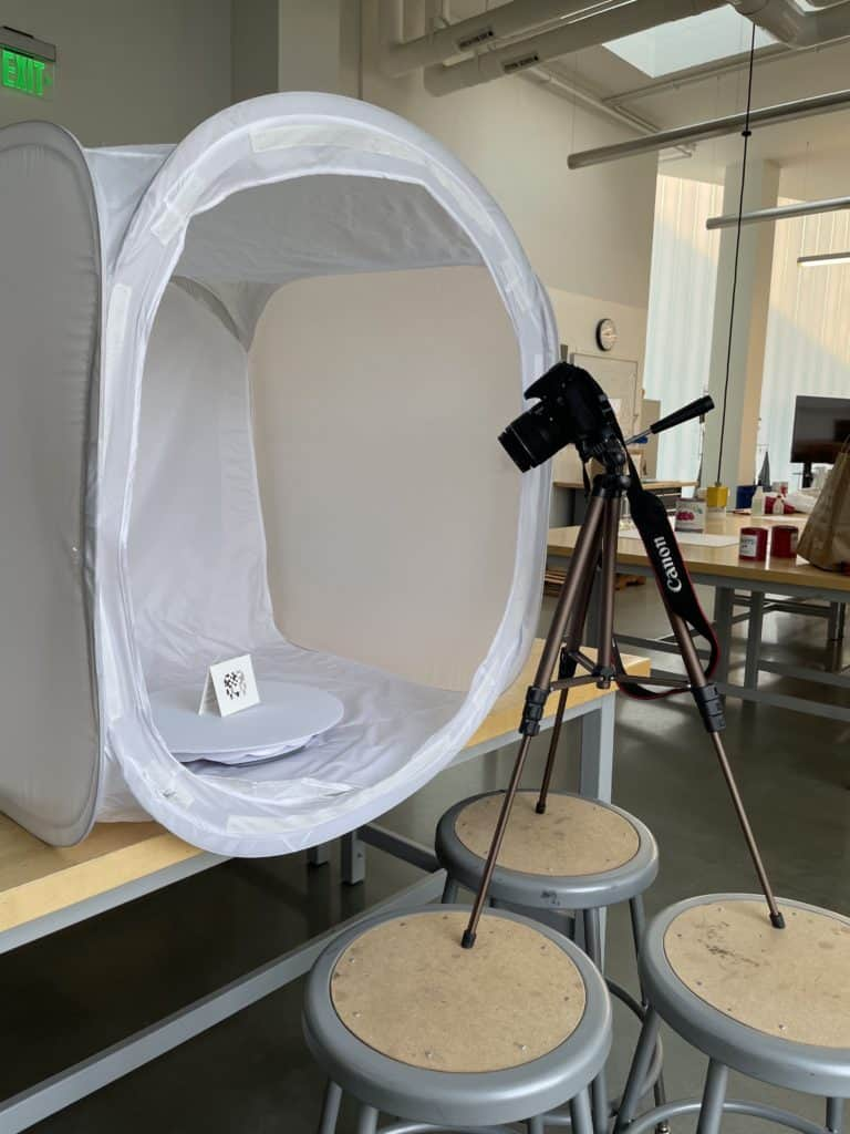 Video production studio setup with a camera, tripod, photo lightbox and turntable.